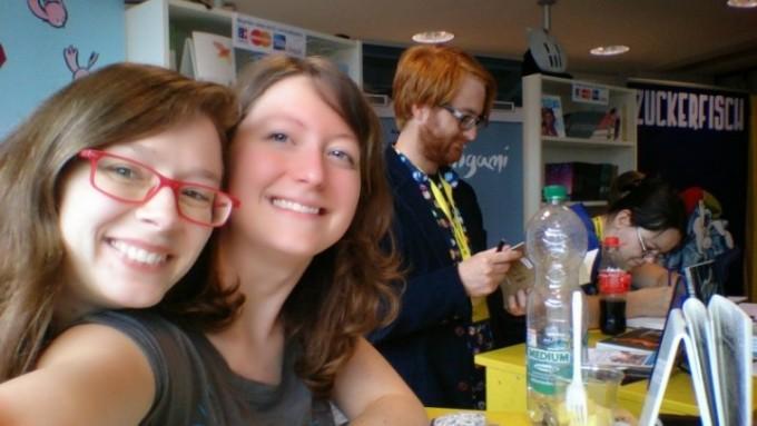 Asja lugt von links über die Schulter ihrer oh-Kollegin Caro. Ebenfalls im Bild Christoph und Lew aus der oh-Crew... besser hätte unser Stand auf dem Comicsalon Erlangen 2014 nicht aussehen können
